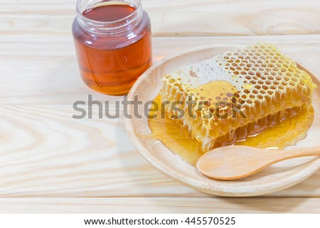 Honeycomb and wooden spoon in wood dish and jar with honey on wooden background. - stock photo