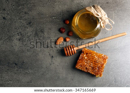 Honeycomb, glass pot with honey and nuts on gray background - stock photo