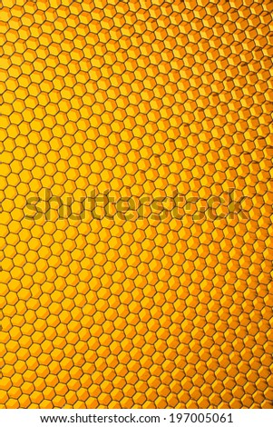 Honeycomb grid against yellow background close up - stock photo
