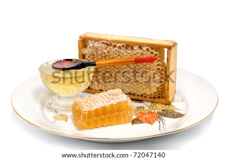 honeycomb in border with honey on dish - stock photo