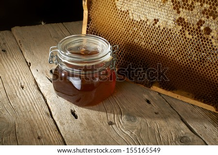 honeycomb on frame with fresh honey in a vase on wooden table.