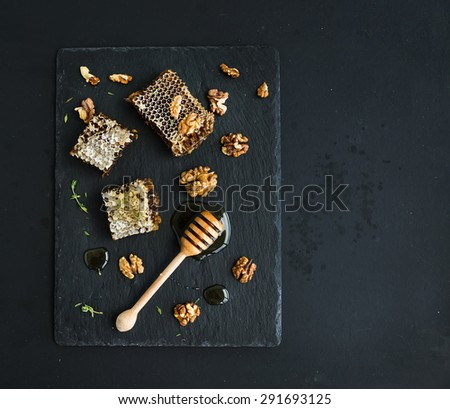 Honeycomb, walnuts and honey dipper on black slate tray over grunge dark backdrop, top view, copy space - stock photo