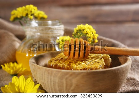 Honeycomb with dipper and jar of honey on sackcloth, close-up - stock photo