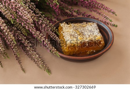 Honeycomb with heather honey near   flowers on a brown background - stock photo