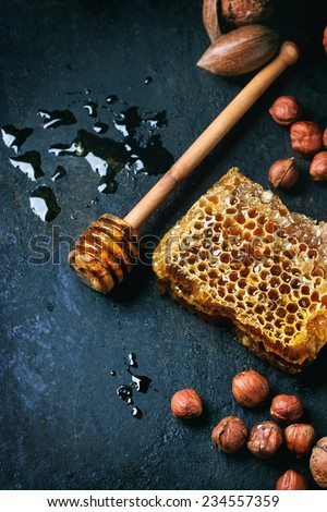 Honeycomb with honey dipper and mix of nuts over black surface. Top view. See series - stock photo