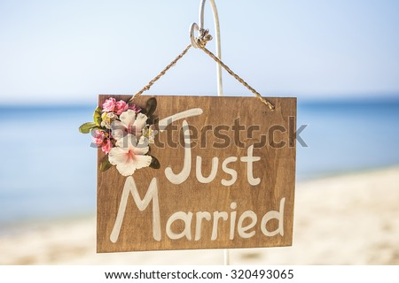 Honeymoon concept. Just married. Wooden plate on the tropical beach. - stock photo