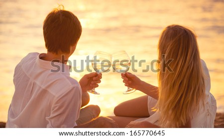 Honeymoon concept, Man and Woman in love, Couple enjoying glass of champagne on tropical beach at sunset, Beautiful sunset light - stock photo