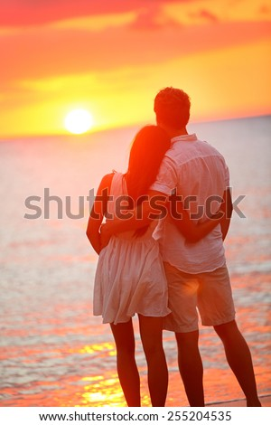 Honeymoon couple romantic in love at beach sunset. Newlywed happy young couple hugging enjoying ocean sunset during travel holidays vacation getaway. Interracial couple, Asian woman, Caucasian man. - stock photo