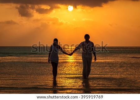 Honeymoon couple walks on the water at sunset holding hands - stock photo