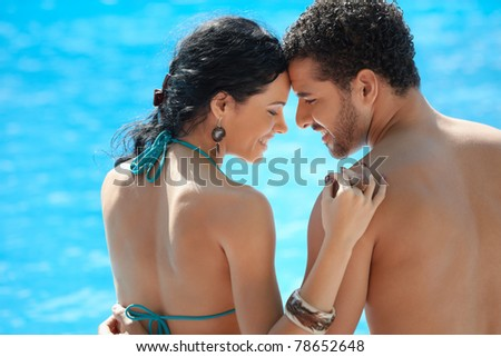 Honeymoon: happy young newlyweds smiling and relaxing near hotel pool. Horizontal shape, rear view, copy space - stock photo