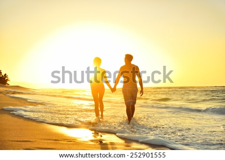 Honeymoon romantic couple in love holding hands walking on beautiful sunset at beach in waterfront. Lovers or newlywed married young couple by the sea enjoying relaxed vacation travel holiday. Hawaii. - stock photo