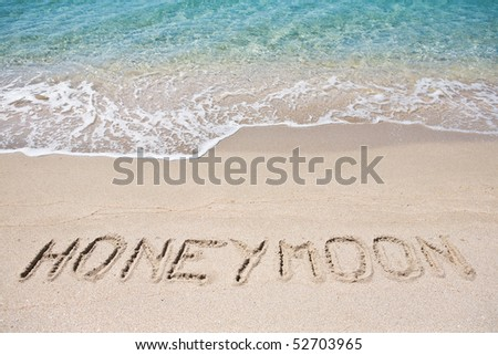 Honeymoon written on the sand - stock photo