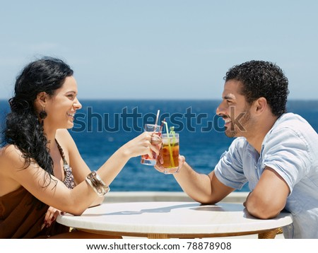 honeymoon: young just married hispanic couple sitting at bar table near the sea and drinking cocktail. Horizontal shape, side view, copy space - stock photo