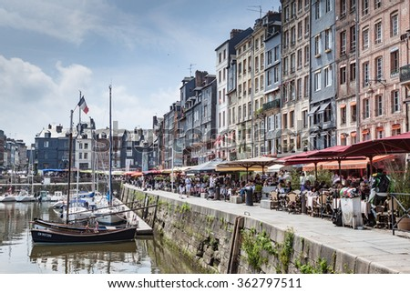 HONFLEUR, FRANCE - JUNE 9, 2010: Boats and harbour in this scenic village on the coast of Normandy,  with people eating at cafes - stock photo