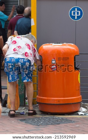 HONG KONG, AUG 20, 2014: Old women collecting bottles from garbage bins in Hong Kong. 1.3 million Hongkongers still live in poverty. - stock photo