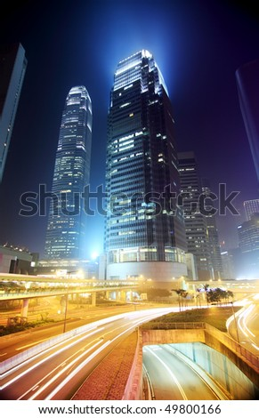 Hong Kong Business District at Night. Corporate building at the back and busy traffic across the main road at rush hour. - stock photo