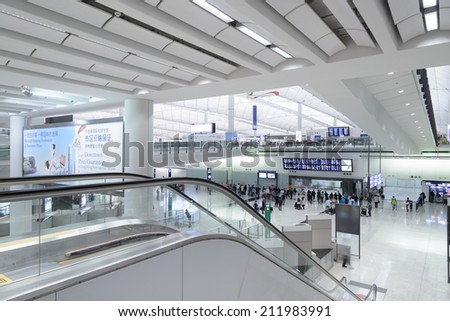 HONG KONG, CHINA - APRIL 14: Passengers in the airport main lobby on April 14, 2014 in Hong Kong, China. The Hong Kong airport handles more than 70 million passengers per year. - stock photo