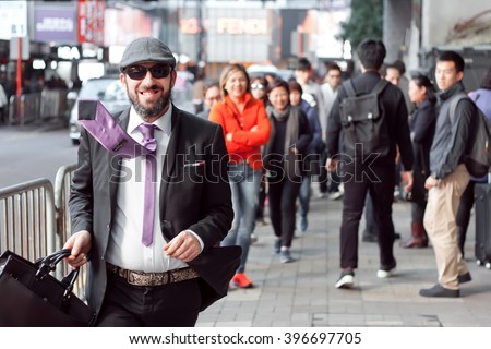 HONG KONG, CHINA - FEB 8: Mime in the role of a businessman with smiley face rushing on busy street of big asian city on February 8, 2016. There are 1,223 skyscrapers in Hong Kong.