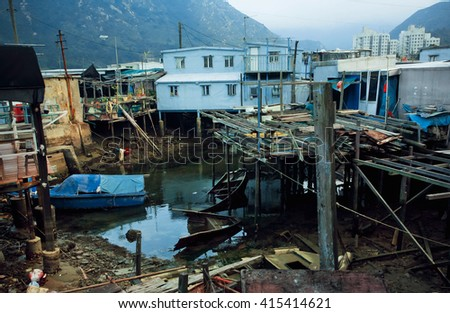 HONG KONG, CHINA - FEB 11: Poor iron houses on riverbank of fishermen village Tai O between mountains on February 11, 2016. Hong Kong dollar is the eighth most traded currency in the world.