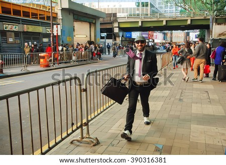 HONG KONG, CHINA - FEB 8: Young businessman with smiley face rushing on busy street of big asian city on February 8, 2016. There are 1,223 skyscrapers in Hong Kong. - stock photo