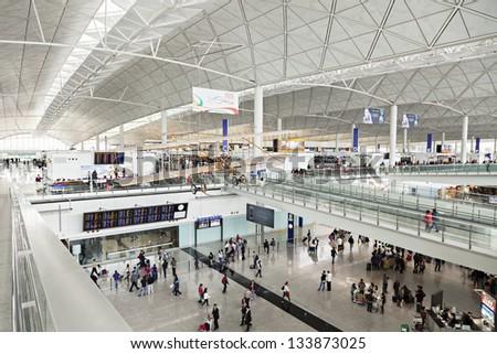 HONG KONG, CHINA - FEBRUARY 21: Passengers in the airport main lobby on February 21, 2013 in Hong Kong, China. The Hong Kong airport handles more than 70 million passengers per year. - stock photo