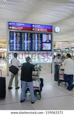 HONG KONG, CHINA - FEBRUARY 11: Passengers in the airport main lobby on February 11, 2013 in Hong Kong, China. The Hong Kong airport handles more than 70 million passengers per year.  - stock photo