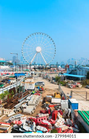 HONG KONG, CHINA - 18 JAN 2015: Massive ferris wheel dominates the skyline with construction mess on the front, in Hong Kong, China. - stock photo