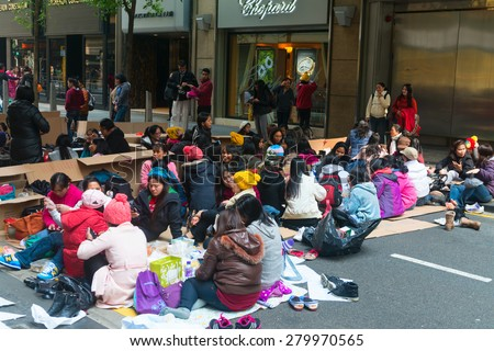 HONG KONG, CHINA - 18 JAN 2015: Meeting of mostly female, Filipino workers on a street in downtown Hong Kong, China. - stock photo