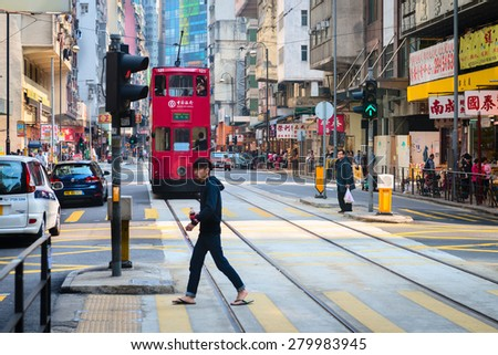 HONG KONG, CHINA - 18 JAN 2015: Pedestrian crossing a typical, busy street in central Hong Kong, China. - stock photo