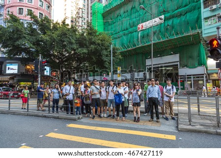 Hong Kong, China - July 2nd. 2016 - Big group of people crossing a street in downtown Hong Kong in Chia, Asia.
