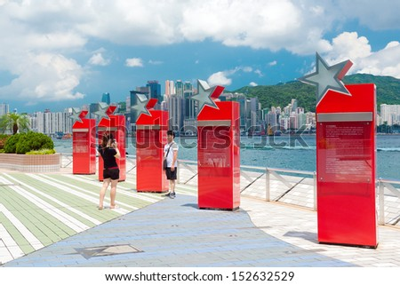 HONG KONG, CHINA - JULY 11: People taking pictures in Avenue of the Stars on July 11, 2013 in Hong Kong, China. Promenade honours celebrities of the Hong Kong film industry as famous city attraction - stock photo