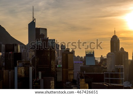Hong Kong, China - July 1st. 2016 - The Hong Kong skyline seen from a rooftop in the sunset on a blue sky day, Hong Kong, China
