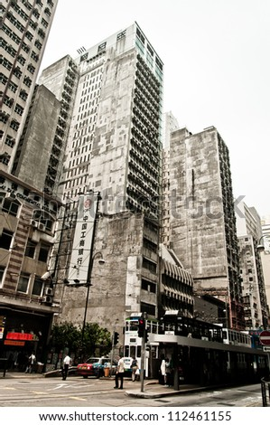 HONG KONG, CHINA - JULY 30, 2012: Street,  trams and buildings on July 30, 2012 in Hong Kong, China. With 7M population and land mass of 1104 sq km, it is one of the most dense areas in the world