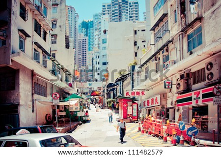 HONG KONG, CHINA - JULY 30: Street view with taxi and buildings on July 30, 2012 in Hong Kong, China. With 7M population and land mass of 1104 sq km, it is one of the most dense areas in the world. - stock photo