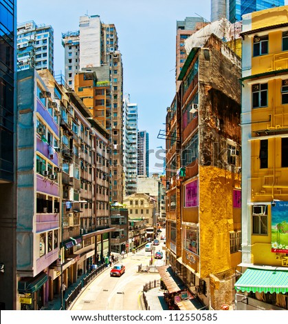 HONG KONG, CHINA - JULY 30, 2012: Street view with taxi and buildings on July 30, 2012 in Hong Kong, China. With 7M population it is one of the most dense areas in the world. - stock photo