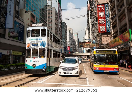 HONG KONG , CHINA - JULY 8 : Transportation system of Hong Kong with the electric trams. Private car and bus. on July 8,2014 in Hong Kong. - stock photo