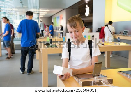 HONG KONG, CHINA - JUNE 18, 2014: Boy looks at the packaging at Apple store in Hong Kong. Store is in a shopping center IFC Mall, it is very popular with locals and tourists visiting Hong Kong. - stock photo