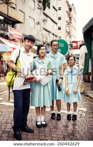 HONG KONG, CHINA - MAY 20, 2014: Group of smiling asian students standing on street of Hong Kong, China on May 20, 2014 - stock photo