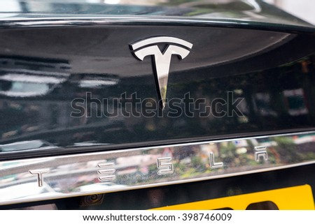 HONG KONG, CHINA - NOVEMBER 21, 2015: Tesla logo on a car. Tesla Motors, Inc. is an American automotive and energy storage company that designs, manufactures, and sells luxury electric cars. - stock photo