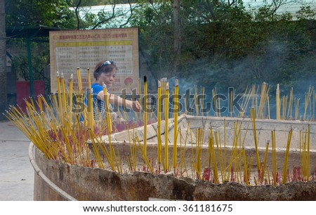 HONG KONG, CHINA - OCTOBER 02, 2015: Devotee offers incense to Tian Tan Buddha (the Big Buddha).