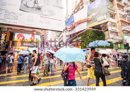 Hong Kong, China - October 03, 2015 : Many people in Mongkok street in rainy day. Mongkok is characterized by a mixture of old and new multi-story building with shops and restaurants at street level. - stock photo
