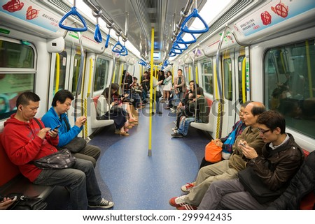 HONG KONG - CIRCA FEBRUARY, 2015: People traveling in the subway and actively use smartphones. Metro aka MRT is the most popular form of public transport in Hong Kong. - stock photo