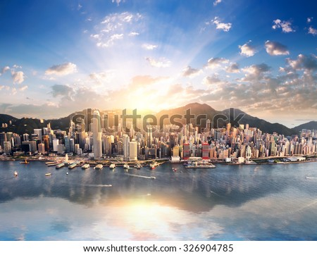 Hong Kong city skyline view from harbor with skyscrapers buildings reflect in water at sunset with sunlight and sun rays shine through clouds on blue sky