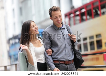 Hong Kong couple shopping in Central walking in streets with shopping bags. Urban mixed race Asian Chinese woman shopper and Caucasian man smiling happy living in city. - stock photo