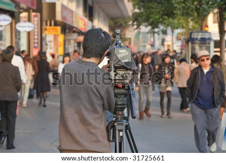 HONG KONG - DECEMBER 23: Cameraman Guorong Zhang is shooting a street scene for the Chinese Reality TV on December 23, 2008 in Kowloon, Hongkong. - stock photo