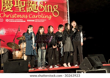 HONG KONG - DECEMBER 23: Chinese Girls sing Christmas songs on a Public Appearance on December 23, 2008 in Kowloon, Hong Kong. - stock photo