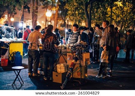 HONG KONG - FEBRUARY 20, A vendor serves a customer on a street at Tuen Mun, Hong Kong on 20 February, 2015. It is a unique street culture during the Chinese New Year holiday. - stock photo