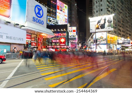 HONG KONG - FEBRUARY 07: People walking across Hennessy Road, Causeway Bay in front of a big department store Sogo at Day. Hong Kong February 07, 2015 - stock photo