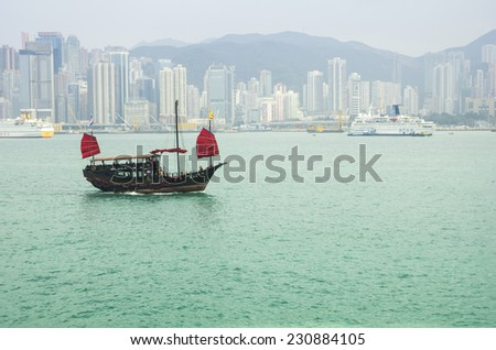 HONG KONG - FEBRUARY 25: The junk boat  in Victoria harbor on February 25, 2013 in Hong Kong. A red chinese traditional junk boat, Aqua Luna, is one of famous tourist attraction - stock photo
