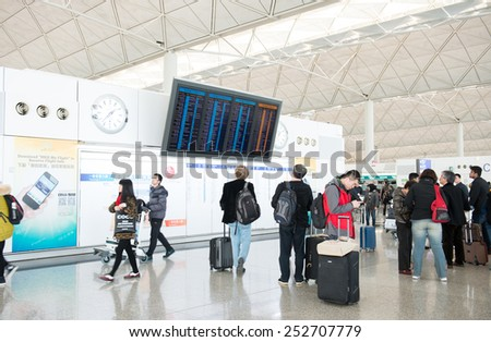 HONG KONG - FEBRURAY 07 : Many traveler with backpack in airport near flight timetable on Februray 07,2015 in Hong Kong. - stock photo